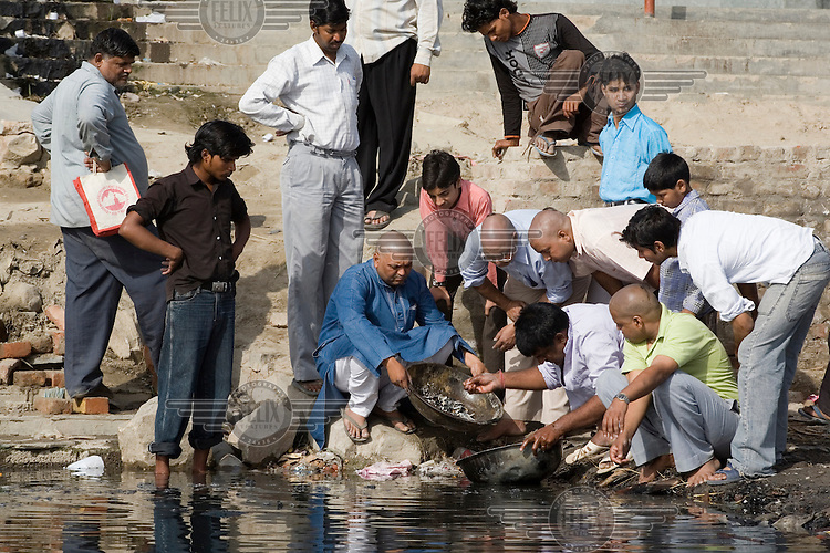 A group of men perform a cremation ritual in the Yamuna River at Nigambodh Ghat.
