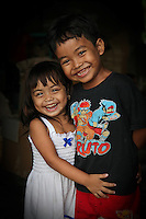 Young Balinese village children stand in the doorway of their home and enjoy the opportunity to pose in front of a camera.