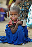 A newly arrived Somali girl relishes a drink of water as she waits with her family to be processed in the reception center of the Dagahaley refugee camp, part of the Dadaab refugee complex in northeastern Kenya.