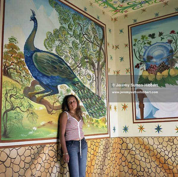 "Nadia, a 14 years old Roma girl, stands  posing like a ""western"" model in front of a mural depicting a peacock painted on the wall of her parents home, in the new part of Sintesti Roma camp. Two weeks after this picture was taken Nadia was due to be married..."