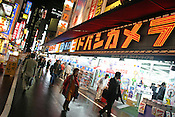Pedestrians walk past the huge 'Yodobashi' electronics store selling cameras, computers and all manner of electronic goods, in the Nishi-Shinjuku district of Tokyo, Japan.