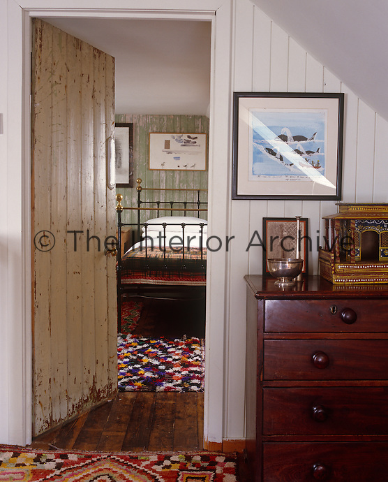 A simple bedroom glimpsed through an open door from the corridor