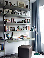 Custom made metal and wood shelving in the study includes an extended shelf which acts as a writing desk