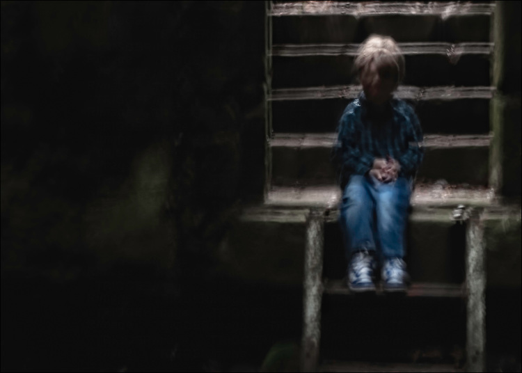 A young child sitting on wooden stairs
