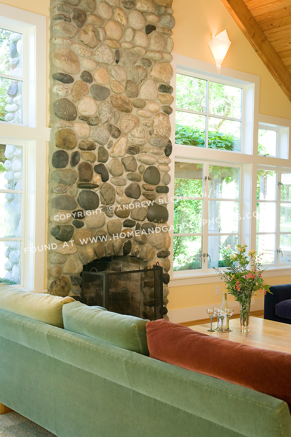 The large rock fireplace and chimney in the living room (LR) of this waterfront weekend vacation retreat on Washington State's Vashon Island adds cozy warmth and ambience on cold winter days.