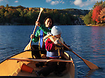 Smiling young woman and a three year old boy paddling a canoe. Fall nature scenery, Killarney Provincial Park, Ontario, Canada.