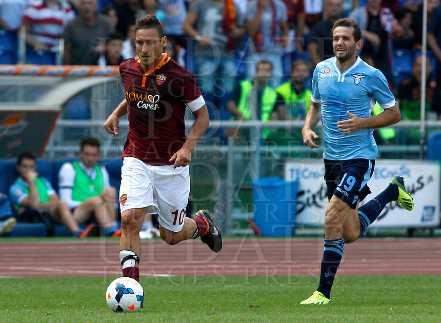 Calcio, Serie A: Roma vs Lazio. Roma, stadio Olimpico, 22 settembre 2013.<br /> AS Roma forward Francesco Totti is chased by Lazio midfielder Senad Lulic, of Bosnia, right, during the Italian Serie A football match between AS Roma and Lazio, at Rome's Olympic stadium, 22 September 2013.<br /> UPDATE IMAGES PRESS/Riccardo De Luca