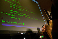 An attendee of the 6th edition of HOPE, an annual hackers' convention, watches code appear on a screen during the event's closing ceremony, July 23rd 2006, New York City, USA.