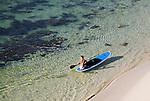 A boy paddles a board along Prevelly Park Beach.  Margaret River, Western Australia, AUSTRALIA.