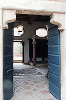 Double doors open into the stables which have floors of red stone incorporating a striking chain motif
