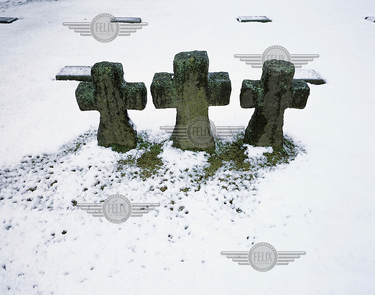 "Gravestones in a snow-covered Flanders Fields cemetery in Langemark. ""Flanders Fields"" is a term used for the area around Ypres in Belgium, where Allied and German soldiers died in their hundreds of thousands in trench warfare during First World War (WWI)....."