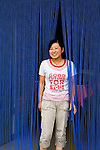 A young Chinese Mongolian woman standing in doorway of her restaurant in the town of Bayan Ul Hot, Inner Mongolia, China.