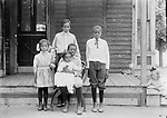 THE THOMAS CHILDREN AND FRIENDS. Cora and Alonzo (Lon) Thomas operated a small grocery from the front room of this house at 715 C Street. Four of their five children are portrayed here. Baby Lonnie, born in 1909, sits on Herschel's lap. Agnes stands at left, and eldest son Wendell stands at the center. The young man at right is probably Lucius Knight, their mother's half brother. Wendell worked a typical variety of jobs in Lincoln--waiter, clerk, porter, laborer, and janitor--before founding the Thomas Funeral Home in Omaha. The Thomas family and many other African American families lived in the South Bottoms, a neighborhood mainly of Germans from Russia, Lincoln's largest immigrant group. The little blonde girl who leans into the right edge of this view serves as a reminder that Lincoln's residential neighborhoods were not segregated by race in the early 20th century--poor people of many ethnicities lived together. A few years later and through the middle third of that century, residential segregation became prevalent in Lincoln. A close-knit black neighborhood arose from that adversity, centered around Twenty-first and T Streets.<br /> <br /> Photographs taken on black and white glass negatives by African American photographer(s) John Johnson and Earl McWilliams from 1910 to 1925 in Lincoln, Nebraska. Douglas Keister has 280 5x7 glass negatives taken by these photographers. Larger scans available on request.