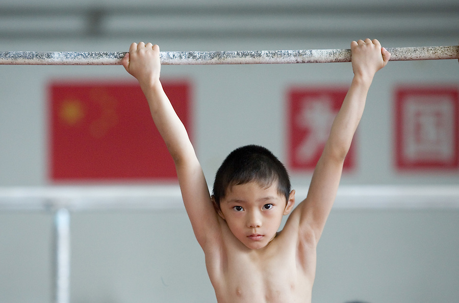 A young boy trains at a gymnastics a sports school in Beijing.