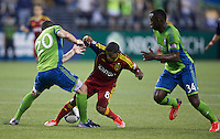 Joao Plata, center, of Real Salt Lake battles Zach Scott, left, of the Seattle Sounders FC and Jhon Kennedy Hurtado of the Seattle Sounders FC during play at CenturyLink Field in Seattle Friday September 13, 2013. The Sounders won the match 2-0.