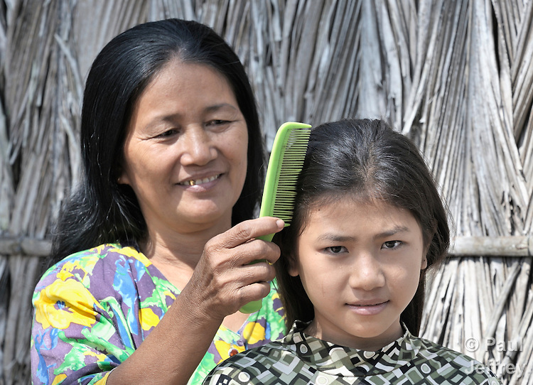 Kim Seng combs the hair of her daughter, Sum Thida, 12, beside their home in Soepreng, a village in the Kampot region of Cambodia.
