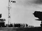 "A captured Japanese photograph shows crewmembers waving to planes launching the surprise attack on Pearl Harbor. The caption reads: ""The moment at which the Hawaii surprise attack force is about to take off from the carrier...On the faces of those who go forth to conquer and those who send them off there floats only that beautiful smile which transcends death..."""