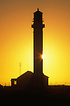 The sun sets behind the silhouette of the Point Arena Lighthouse on the Northern California Coast south of Mendocino. The original Point Arena Lighthouse was damaged in the 1906 Earthquake the United States Lighthouse Service contracted with a San Francisco based company that built factory smokestacks to build a replacement. The new Point Arena Lighthouse began operation in 1908 and was the first lighthouse to be built with steel reinforcement rods encased in concrete to help it withstand an earthquake. Photographed 07/03