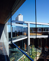 The two-storey courtyard at the centre of the house is surrounded by glass walls so that the interior becomes the exterior