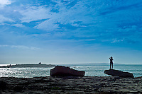 Woman taking photographs of the Arran Isles at Doolin tourist resort in County Clare, West Coast of Ireland