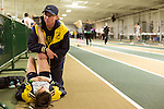 January 25, 2014. Winston Salem, North Carolina.<br /> Coach Patrick Cromwell stretches Kayla Montgomery before she was to run in the 1600m at the 2014 David Oliver Classic. Cromwell has been integral to Kayla's advancement as a runner since her MS diagnosis.<br />  3 and a half years ago, during an examination after sustaining tailbone and head injuries from a fall during a soccer game, Kayla Montgomery, now 18, was diagnosed with multiple sclerosis. Montgomery, then a decent runner, refused to be limited by her diagnosis, and after years of training has become one of the best high school runners in the country.