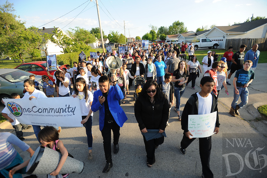 NWA Democrat-Gazette/ANDY SHUPE - Irvin Camacho leads a large crowd Tuesday, April 21, 2015, during A Walk for Peace, a community walk organized by Camacho in the wake of two recent fatal shootings in Springdale. The walk began at Luther George Park and stopped at the sites of the shootings. Visit nwadg.com/photos to see more photographs from the march.