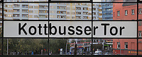 Station sign at Kottbusser Tor U-Bahn station or underground train station, with a view of the Kreuzberg district through the window, Berlin, Germany. The station is on 2 levels with a viaduct across Skalitzer Strasse. Picture by Manuel Cohen