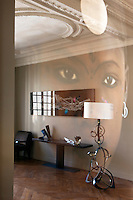 The wall of the entrance hall reflects a portrait and an image of a floating piece of wood by Antoine Schneck, with a bronze sculpture by Etienne Viard on the console table and a bronze floor lamp by Van der Straeten