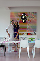 Karim Rashid and his wife Ivana standing in front of an artwork in the dining area