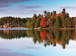 Colorful autumn trees reflecting in a lake. Beautiful fall nature scenery. George lake, Killarney Provincial Park, Ontario, Canada