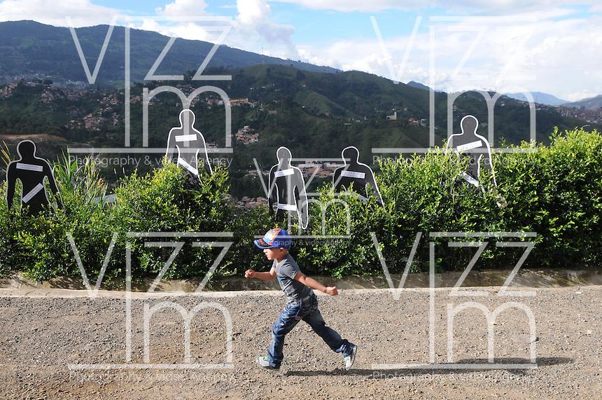 """MEDELLÍN - COLOMBIA, 07-06-2014. Un niño pasa frente a las fotos con los nombres de las personas desaparecidas en """"La Escombrera"""", en la Comuna 13 de Medellín, durante una vigilia contra las desapariciones forzadas. En 2002, Medellín fue sacudido por la violencia después de la decisión del Gobierno de recuperar un sector de la ciudad disputada por los paramilitares de derecha y las milicias de izquierda. Según los familiares de las víctimas, en la operación ordenada el 16 de octubre de 2002 por el presidente Álvaro Uribe, decenas de personas murieron, más de 100 personas resultaron heridas, 98 personas desaparecieron y más de 200 familias fueron desplazadas./  A boy walks in front of the images with the names of missing persons in """"La Escombrera"""" in Comuna 13 in Medellín, during a vigil against forced disappearances. In 2002, Medellín was rocked by violence following the government's decision to recover a part of the city disputed by right-wing paramilitaries and leftist militias. According to relatives of the victims, the orderly operation on October 16, 2002 by President Alvaro Uribe, dozens of people were killed, over 100 people were injured, 98 people missing and more than 200 families were displaced. Photo: VizzorImage/Luis Rios/STR"""
