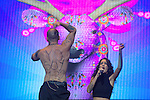 Calle 13's lead singer  Rene Perez  shows his back with the legend #Iam132, a hashtag that represents the emerging student movement in Mexico, while Ileana Cabra sings next to him, during the Wirikuta Fest in Mexico City's Foro Sol, May 26, 2012. Almost sixty thousand people attended the Fest to support the struggle of the Wixarica Native people against the trasnational mining corporations. Photo by Heriberto Rodriguez