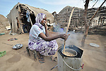 A woman cooks a meal on an improved stove in the Goz Amer refugee camp in eastern Chad. More than a quarter million residents of Darfur live in camps in Chad, along with almost 200,000 Chadians who have been internally displaced by related violence. Such stoves are given to refugee women so that they'll consume less firewood, which means fewer trips outside the camp to forage for fuel, trips which frequently subject the women to assault and rape.