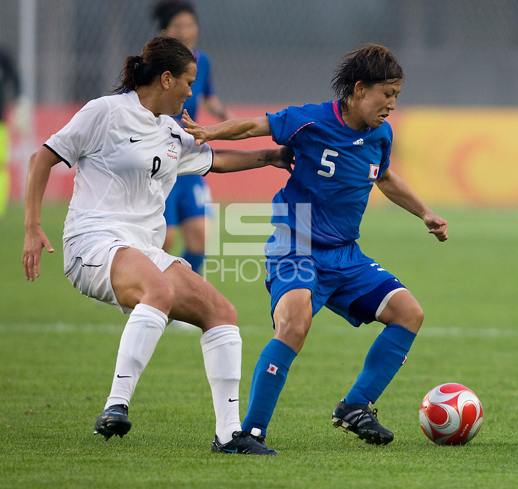 New Zealand forward (9) Amber Hearn tries to keep tight to Japanese midfielder (5) Miyuki Yanagita during first round play in the 2008 Beijing Olympics at Qinhuangdao, China. .  Japan tied New Zealand, 2-2, at Qinhuangdao Stadium.