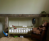 An antique child's bed and 1920s French armchair in a guest bedroom; the chestnut beams are antique