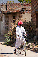 Indian man in traditional clothing riding bicycle in Jawali village in Rajasthan, Northern India