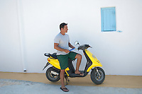man reading a map while on a moped in Greece
