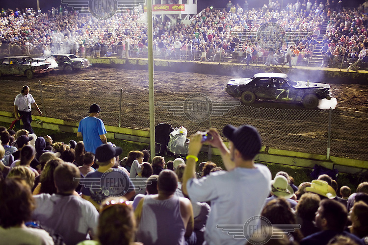 "A spectator takes a picture at ""Smash Your Clunker"" Demolition Derby, an annual competition, at the Hopkinton State Fair in Hopkinton, New Hampshire. Competitors this year have had an especially difficult job finding big, old, American cars to compete with because of the Cash for Clunkers program."
