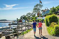 Par promenerar hand i hand på grusväg på Dalarö strandväg i Stockhjolms skärgård.