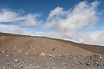 Mauna Kea, Big Island of Hawaii, Hawaii; barren rock and dirt alongside the road up to the Mauna Kea Observatories (MKO), currently there are 13 independent multi-national astronomical research facilities located on the summit. Mauna Kea's altitude and isolation in the middle of the Pacific ocean make it an ideal location for astronomical observation.