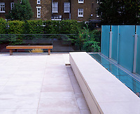 A panel of hardened sandblasted glass provides an element of privacy to the seating area on the roof terrace.