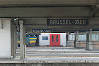 A regional passenger train waits on the far track in Brussels-South Station.
