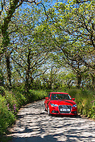 Driving a red German Audi saloon car along country lane at Hartland in North Devon, Southern England, UK