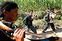 Members of the People?s Liberation Army, the Maoist rebels that have been fighting for control of the country, patrol a remote part of western Nepal on June 21, 2006. The ten-year old conflict in Nepal has claimed an estimated 13,000 lives. (Photo/Scott Dalton)