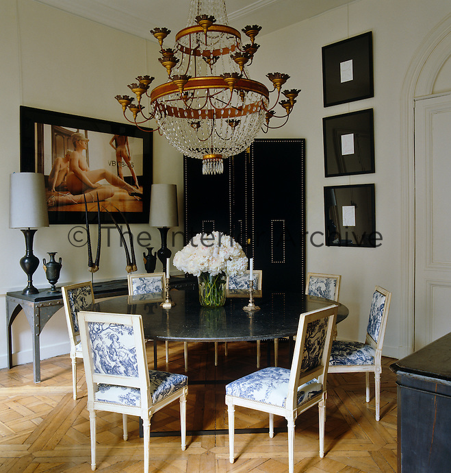 The dining room is furnished with a circular Belgian stone table and Louis XVI-style chairs upholstered in a toile de Jouy with a 17th century crystal Italian chandelier hanging from the ceililng.  The photograph is by Herb Ritts