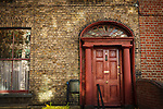 2012: Dublin, Ireland. An old and collapsing red door on a brown brick house as the warm Autumn Sun shines dappled light on the facade<br />