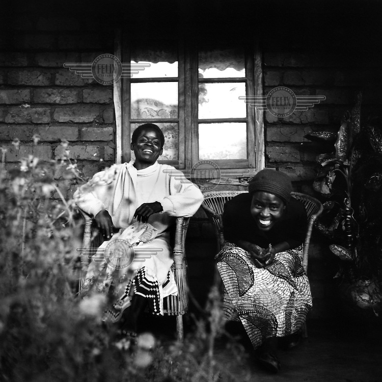 A portrait of two women sitting outside a house by a window. They are outpatients from the mental health centre at Zomba hospital.