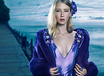 Beauty portrait of a young beautiful blond woman wearing a blue evening dress and a fur jacket outdoors at waterfront