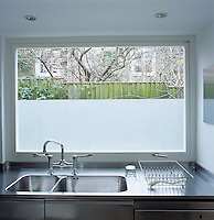 This kitchen window beyond the stainless steel sink is partly frosted for privacy