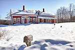 A snow storm covers the ground and an old red antique Cape Cod style home.